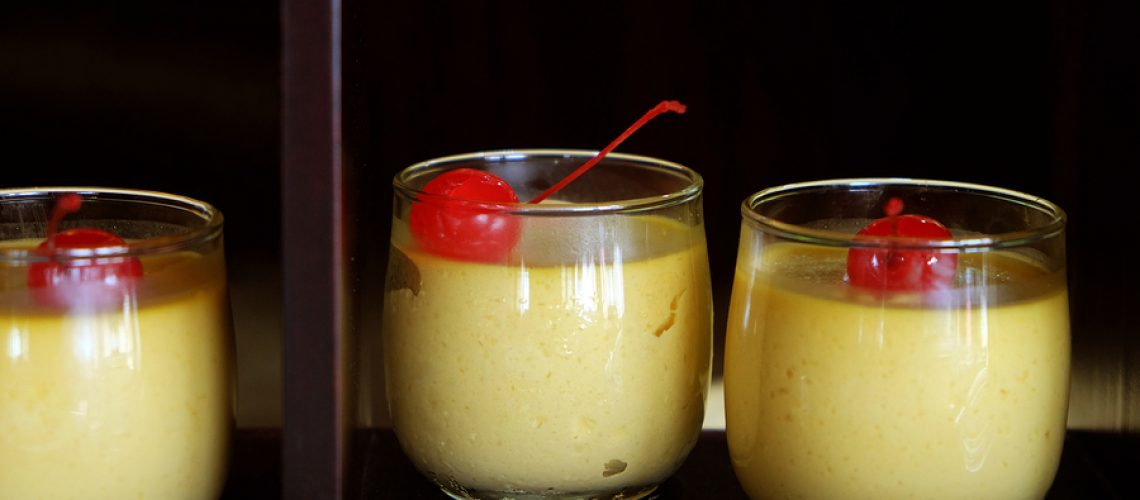 Mango Pudding With Red Cherry Topping In Drinking Glass On Wood